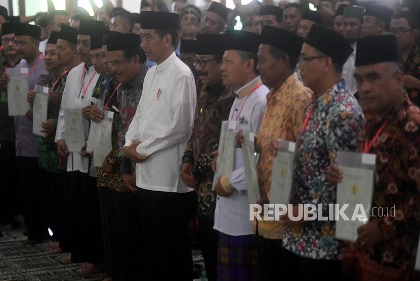 Presiden Joko Widodo (tengah) berfoto bersama para perwakilan penerima sertifikat tanah wakaf usai pembagian di Masjid Baiturrahman, Ngawi, Jawa Timur, Jumat (1/2/2019).