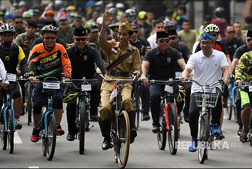 Presiden Joko Widodo (tengah) didampingi Gubernur Jawa Barat Ridwan Kamil (kanan) menyapa warga ketika mengikuti kegiatan sepeda bersama dengan tema Bandung Lautan Sepeda di Bandung, Jawa Barat, Sabtu (10/11)