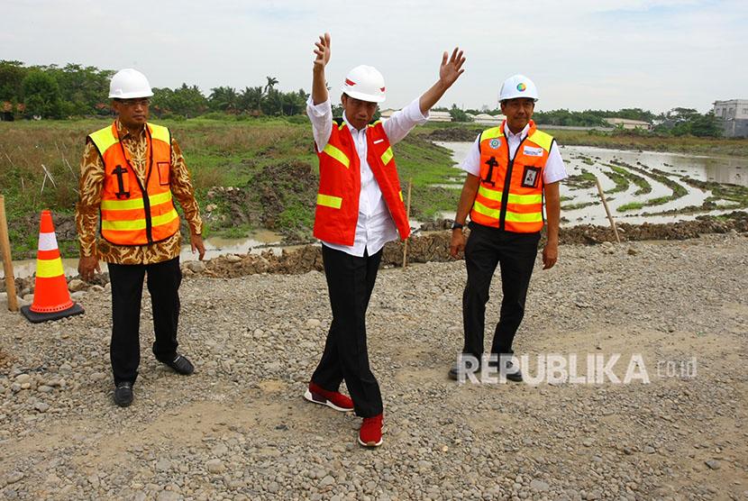 President Joko Widodo (center) accompanied by Transportation Minister Budi Karya Sumadi (left) and President Director of PT. Angkasa Pura II Muhammad Awaluddin (right) oversee the construction of Soekarno-Hatta Airport's third runway, Tangerang, Banten, Thursday (June 21).