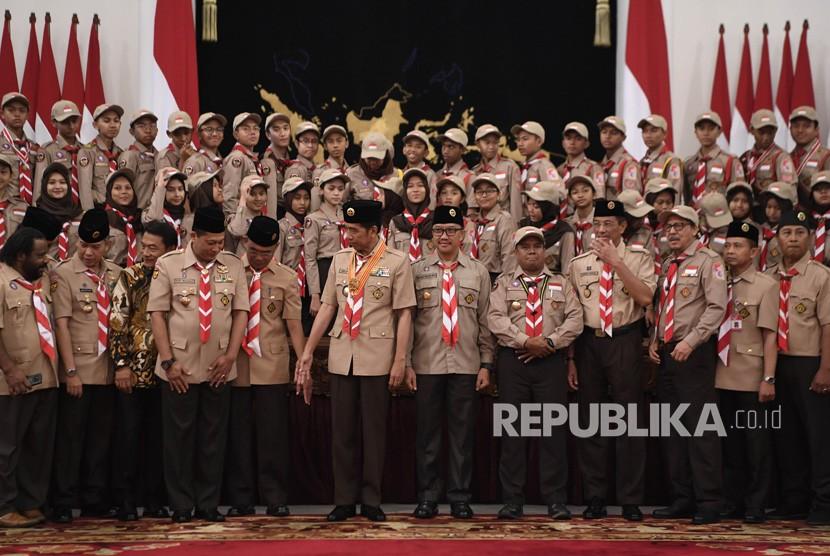 Presiden Joko Widodo (tengah) didampingi Menpora Imam Nahrawi (keenam kanan), Mendikbud Muhadjir Effendy (kelima kiri) dan Ketua Kwarnas Pramuka Komjen Pol (Purn) Budi Waseso (keempat kiri) foto bersama dengan Kontingen Gerakan Pramuka Indonesia usai upacara pelepasan menuju Jambore Pramuka Dunia XXIV di Istana Negara, Jakarta, Jumat (19/7/2019).