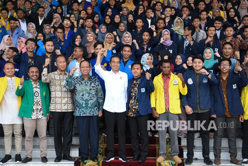 Presiden Joko Widodo (tengah) didampingi Menristek Dikti M Nasir (keempat kiri) dan Menteri Sosial Agus Gumiwang (ketiga kiri) berfoto dengan peserta Konferensi Mahasiswa Nasional ketika diterima di Istana Bogor, Jawa Barat, Jumat (7/12/2018).