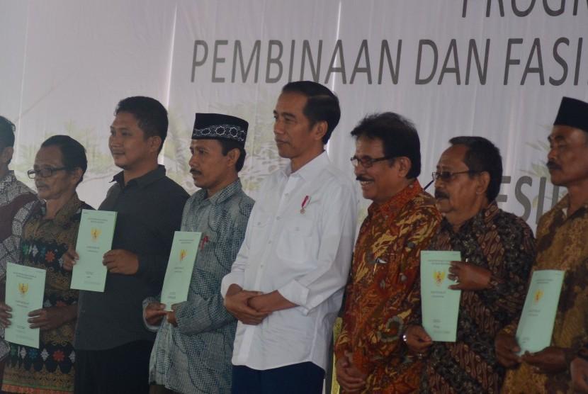 Presiden Joko Widodo (tengah) didampingi Menteri Agraria dan Tata Ruang/Kepala BPN Sofyan Djalil (ketiga kanan) berfoto bersama warga seusai penyerahan secara simbolis sertifikat hak atas lahan tanah di lapangan Pemerintahan Kota Tasikmalaya, Jawa Barat, Jumat (9/6).