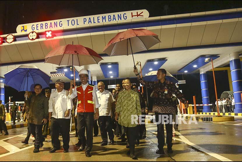 Presiden Joko Widodo (tengah) didampingi Menteri BUMN Rini Soemarno (kedua kanan), Menteri PUPR M. Basuki Hadimuljono (kedua kiri), Seskab Pramono Anung (kiri)  dan Gubernur Sumatera Selatan Alex Noerdin (ketiga kanan) meninjau gerbang tol Palembang saat peresmian jalan tol Sumatra ruas Palembang-Indralaya (Palindra) Seksi I di Desa Ibul Besar, Pemulutan, Ogan Ilir (OI), Sumatra Selatan, Kamis (12/10).