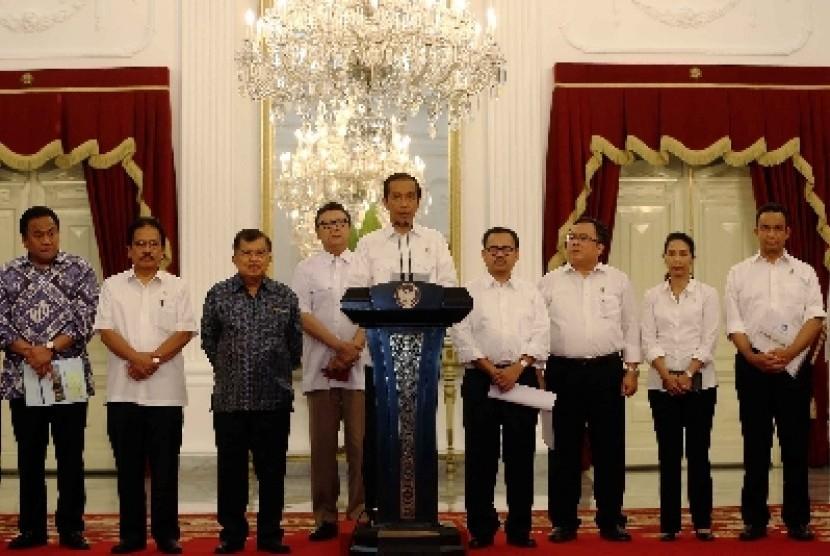 Presiden Joko Widodo (tengah) didampingi Wapres Jusuf Kalla (keempat kiri) dan para Menteri Kabinet Kerja mengumumkan kenaikan harga BBM bersubsidi di Istana Merdeka, Jakarta, Senin (17/11) malam.