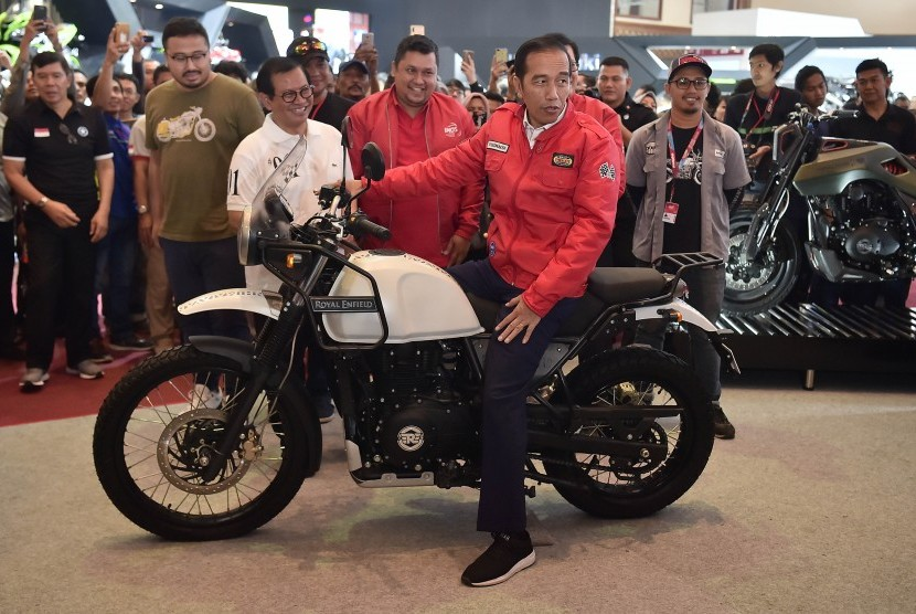 Presiden Joko Widodo (tengah) mencoba motor Royal Enfield saat mengunjungi Indonesia Motorcycle Show (IMOS) 2018 di Jakarta Convention Center, Jakarta, Sabtu (3/11/2018).