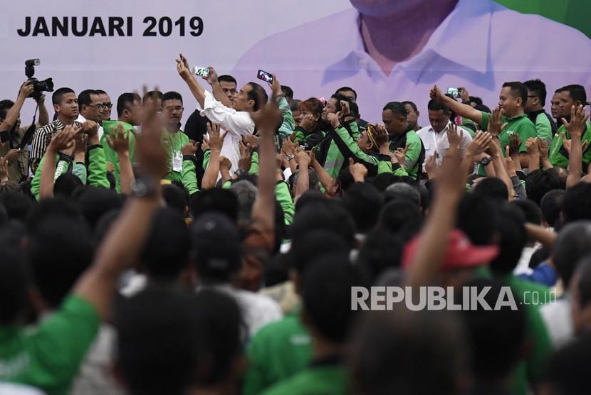 Presiden Joko Widodo (tengah) mengajak para pengemudi online berswafoto usai menghadiri Silatnas Keluarga Besar Pengemudi Online di Jakarta, Sabtu (12/1/2019).