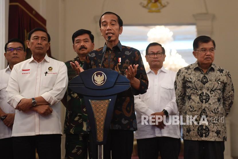 Presiden Joko Widodo (tengah) menyampaikan keterangan terkait kerusuhan pascapengumunan hasil pemilu 2019 di Istana Merdeka, Jakarta, Rabu (22/5/2019).