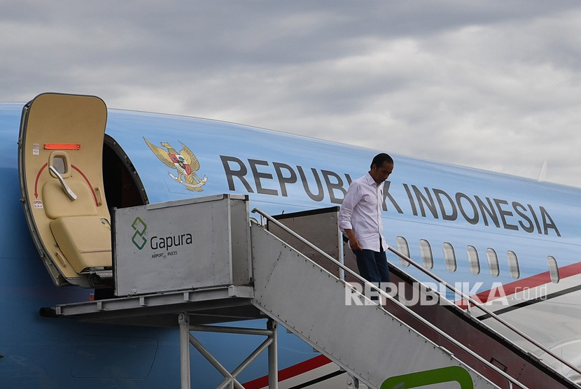 Presiden Joko Widodo menuruni tangga pesawat kepresidenan. Pesawat kepresidenan disebut akan dicat ulang dengan dominasi warga bendera Indonesia, merah putih.