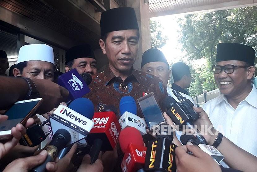 Presiden Jokowi menjabat pertanyaan wartawan usai shalat jumat di Masjid Istiqlal, Jumat (2/3).