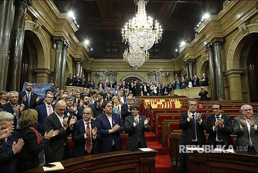 Presiden Katalunya Carles Puigdemont bertepuktangan usai voting pendeklarasian kemerdekaan Katalunya.