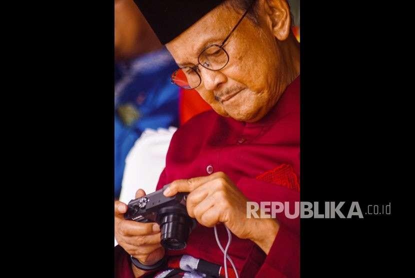 Presiden ke-3 Republik Indonesia B.J. Habibie melihat hasil foto di kamera digitalnya saat menghadiri Peringatan HUT ke-61 Provinsi Riau di Kota Pekanbaru, Kamis (9/8).