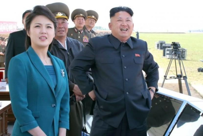 Presiden Korea Utara Kim Jong-un (kanan) bersama istrinya, Ri Sol-ju (kiri).