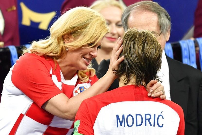 Presiden Kroasia Kolinda Grabar Kitarovic (kiri) saat menghibur kapten Kroasia, Luka Modric.