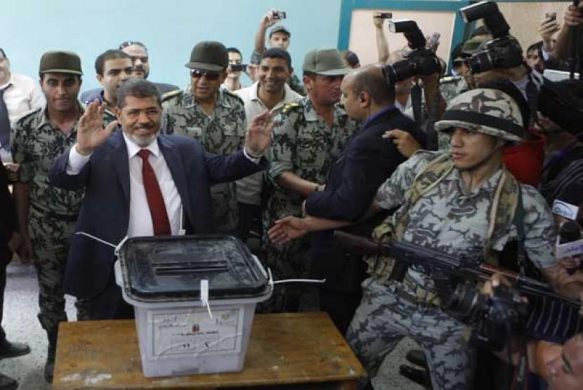 Presiden  Mesir Muhammad Mursi dikawal tentara saat pemilu di Mesir, bulan Juni tahun 2012.