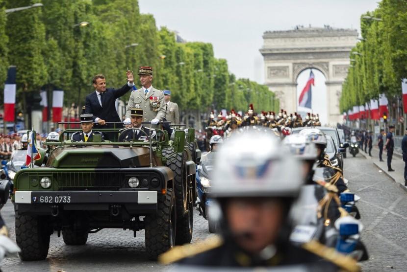 Presiden Prancis Emmanuel Macron memberi isyarat di mobil komandonya di sebelah Kepala Staf Angkatan Darat Prancis Jenderal Francois Lecointre ketika mereka meninjau pasukan sebelum dimulainya parade Hari Bastille di jalan Champs-Elysees di Paris, Ahad (14/7).