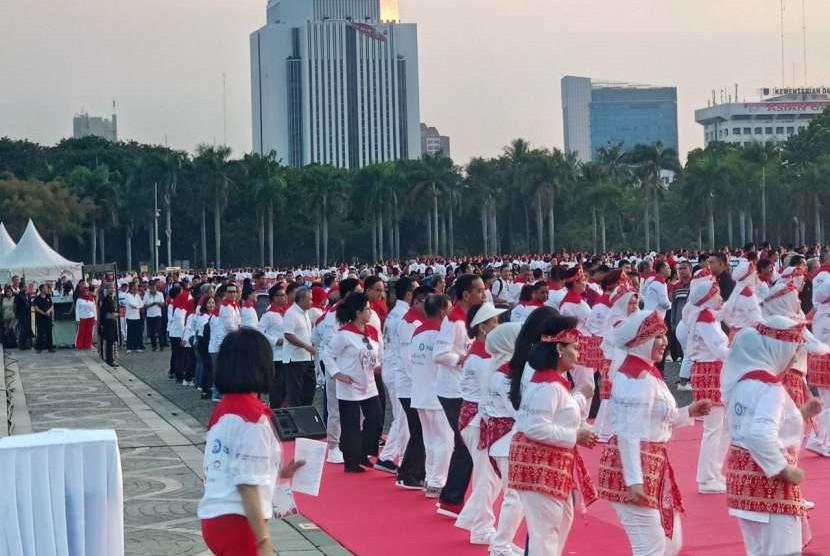Presiden Republik Indonesia Joko Widodo dan sejumlah menteri melakukan senam poco-poco bersama 65 ribu orang di Silang Monumen Nasional, Jakarta Pusat, Ahad (5/8).