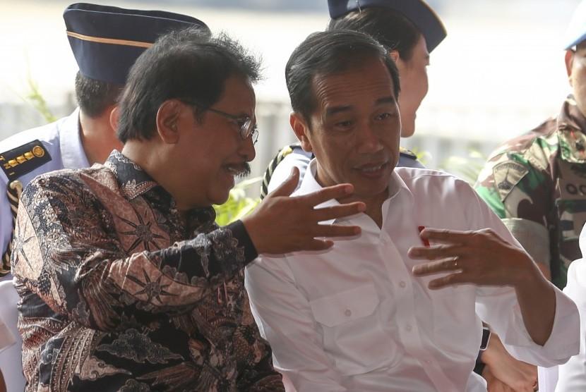Presiden RI Joko Widodo (kanan) berbincang dengan Menteri (ATR/BPN) Sofyan Djalil (kiri) saat penyerahan sertifikat hak atas lahan tanah di pelataran Benteng Kuto Besak (BKB), Palembang, Sumatera Selatan, Jumat (13/7).