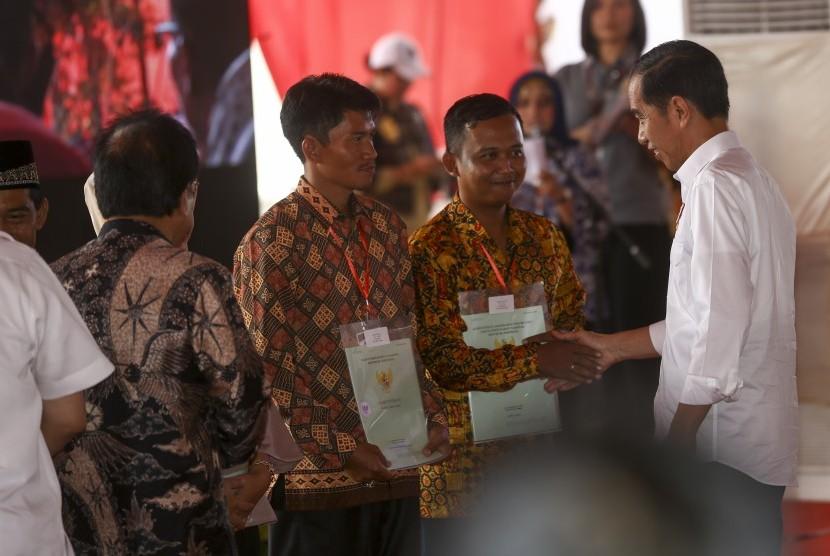 Presiden RI Joko Widodo (kanan) menyerahkan sertifikat hak atas lahan tanah kepada perwakilan masyarakat di pelataran Benteng Kuto Besak (BKB), Palembang, Sumatera Selatan, Jumat (13/7).