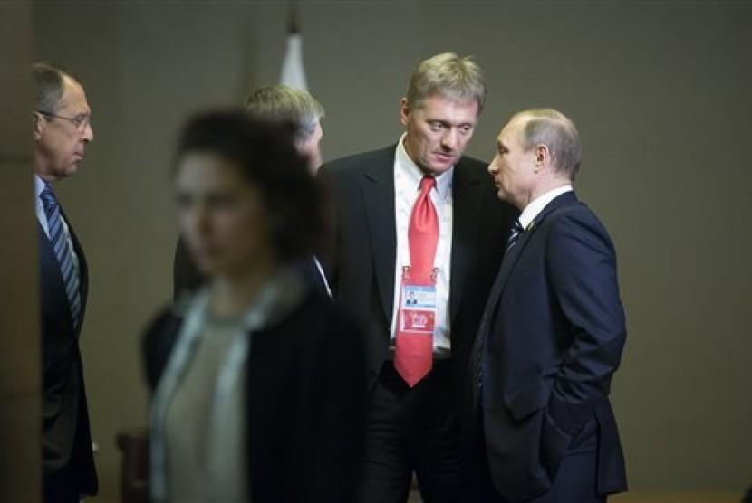 Presiden Rusia Vladimir Putin (kanan) berbicara dengan  juru bicara Kremlin Dmitry Peskov (kedua kanan).
