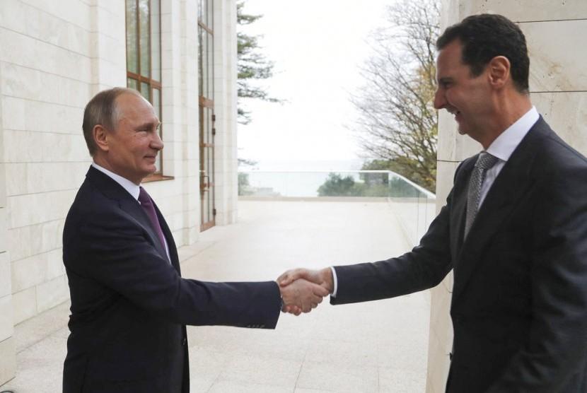 Presiden Rusia Vladimir Putin (kiri) berjabat tangan dengan Presiden Suriah Bashar Assad di kediaman Bocharov Rucheidi resor Laut Hitam Sochi, Rusia, Senin (20/11).