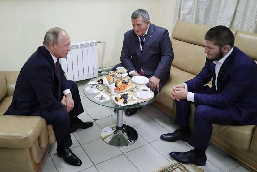 Presiden Rusia Vladimir Putin (kiri) saat berbincang dengan petarung bebas Khabib Nurmagomedov (kanan) dan pelatih serta ayah dari Khabib, Abdulmanap Nurmagomedov (tengah) di Ulyanovsk, Rusia.