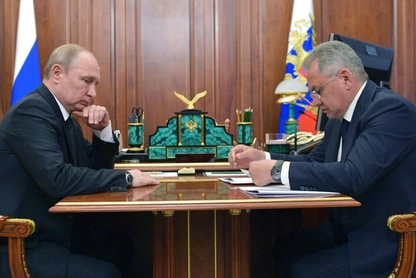 Presiden Rusia Vladimir Putin mendengarkan Menteri Pertahanan Rusia Sergei Shoigu selama pertemuan mereka di Kremlin di Moskow, Rusia, Selasa (2/7). Kebakaran di salah satu kapal selam laut angkatan laut Rusia menewaskan 14 pelaut.