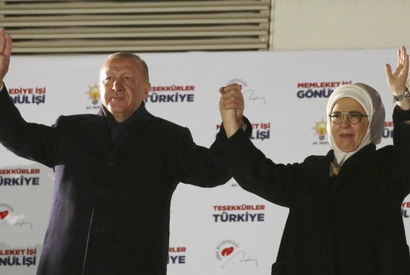 Presiden Turki dan pemimpin Partai AKP Turki Recep Tayyip Erdogan dan istrinya Emine menyapa pendukung usai pengumuman hasil pemilu lokal di Ankara, Turki, Senin (1/4).