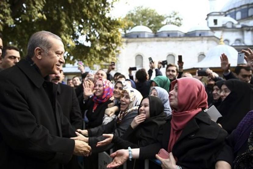 Presiden Turki Recep Tayyip Erdogan berbicara dengan pendukungnya usai shalat pagi di Masjid Eyup Sultan di Istanbul, Senin, 2 November 2015. Partai berkuasa AKP menang 49 persen suara dalam pemilihan parlemen.