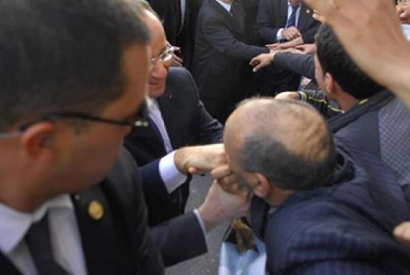 Pria Aljazair cim tangan  Presiden Prancis