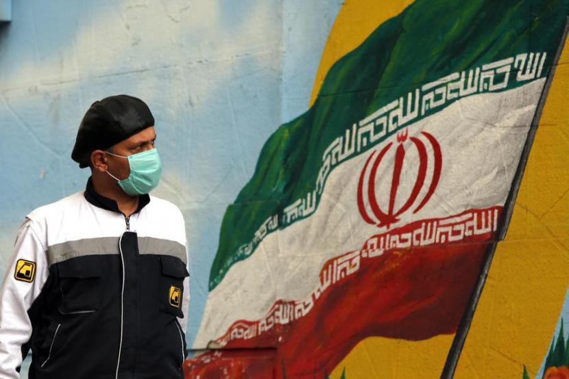 Pria berjalan dengan latar mural bendera Iran. Iran tak izinkan lembaga pemantau nuklir PBB ke pabrik produksi komponen sentrifugal TESA Karaj. Ilustrasi.