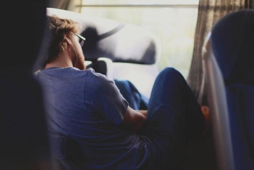 Pria mencoba tertidur saat duduk di atas kendaraan.
