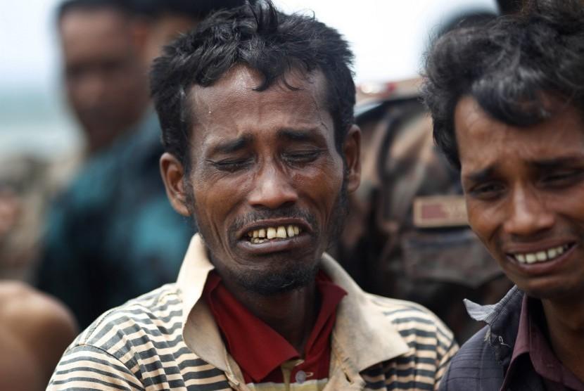Pria muslim Rohingya menangis ketika dipaksa untuk naik kapal untuk dikembalikan ke Myanmar dekat pos penjaga perbatasan di Taknaf,Bangladesh,Jumat (22/6).  (Saurabh Das/AP)