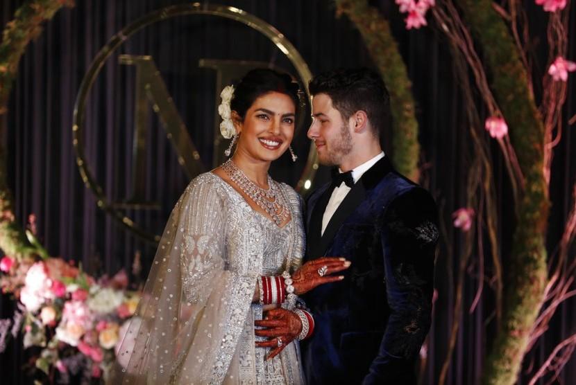 Priyanka Chopra dan Nick Jonas berpose untuk fotografer di resepsi pernikahan mereka di New Delhi, Selasa (4/12).