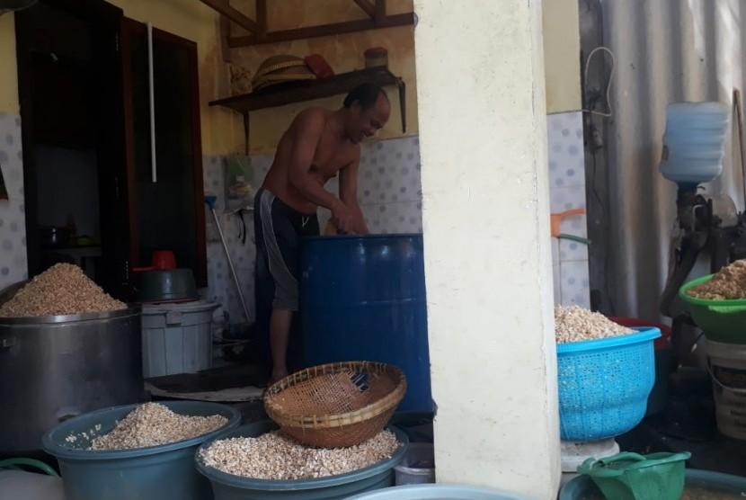 Produsen tempe di Surabaya, Untung Sutopo (49) memilah kacang kedelai sebagai bahan baku pembuatan tempe di kediamannya di Jalan Tenggilis Kauman, Tenggilis Mejoyo, Surabaya, Selasa (10/7).