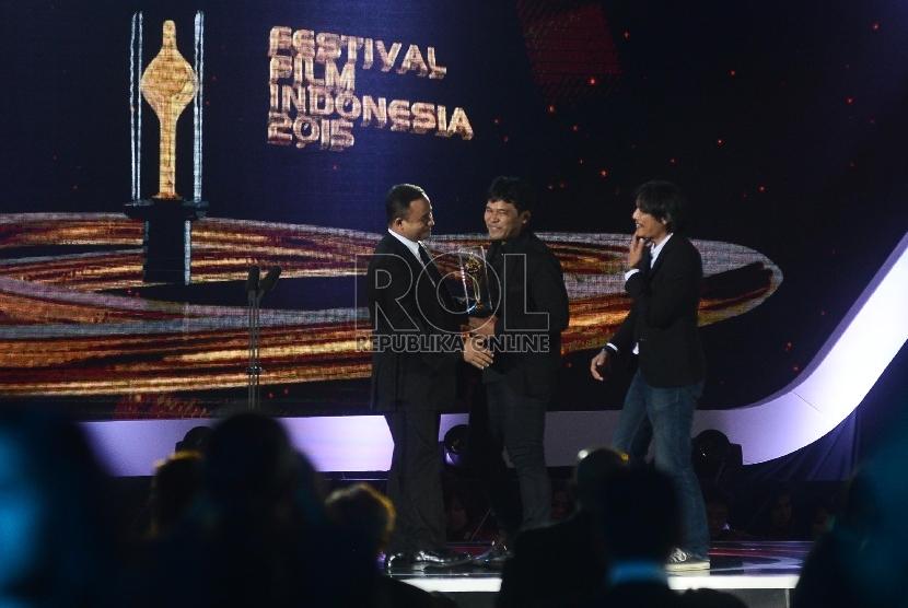Produser film Siti Ifa Isfansyah (tengah) bersama Sutradara film Siti Eddie Cahyono (kanan) menerima piala citra yang diberikan oleh Menteri Pendidikan Anies Baswedan (kiri)dalam Malam Puncak Festival Film Indonesia (FFI) 2015, di Banten, Senin (23/11) m