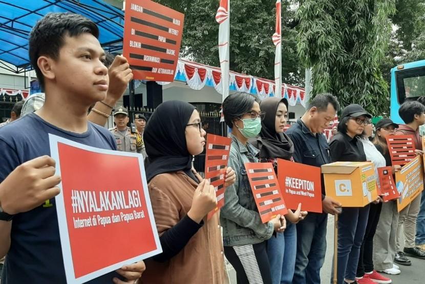 Puluhan orang dari koalisi masyarakat sipil sedang melakukan aksi di depan kantor Kominfo, Jalan Merdeka Barat, Jakarta Pusat, Jumat (23/8). Mereka menuntut agar pemerintah segera menghentikan pemblokiran internet di Papua dan Papua Barat.