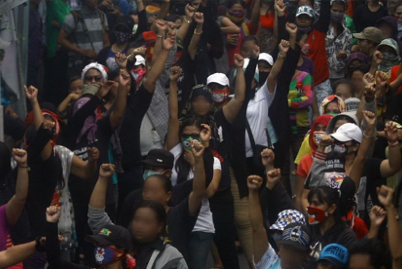 Puluhan Pekerja Seks Komersil (PSK) mengangkat tangan saat mendengarkan orasi usai mengikuti upacara bendera di kawasan lokalisasi Dolly, Surabaya, Jawa Timur, Senin (23/6).