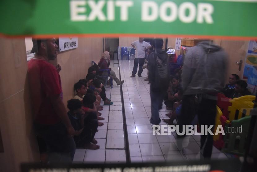 Puluhan pemuda anggota geng motor Jembatan Mampang (Jepang) menunggu pemeriksaan urine seusai penangkapan di Polresta Depok, Jawa Barat, Senin (25/12).