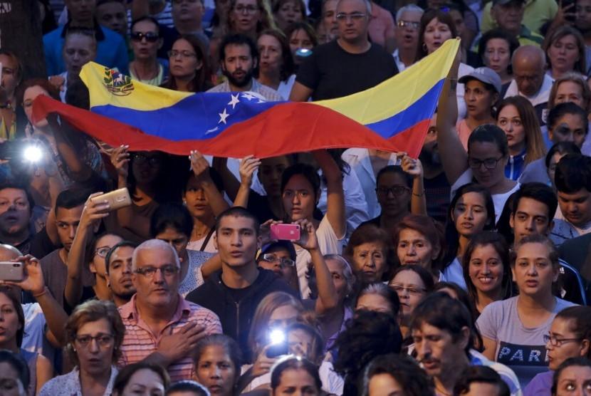 Rakyat Venezuela mendengarkan pidato pemimpin oposisi Juan Guaido yang memproklamirkan diri sebagai presiden di Caracas, Venezuela, Kamis (28/3).