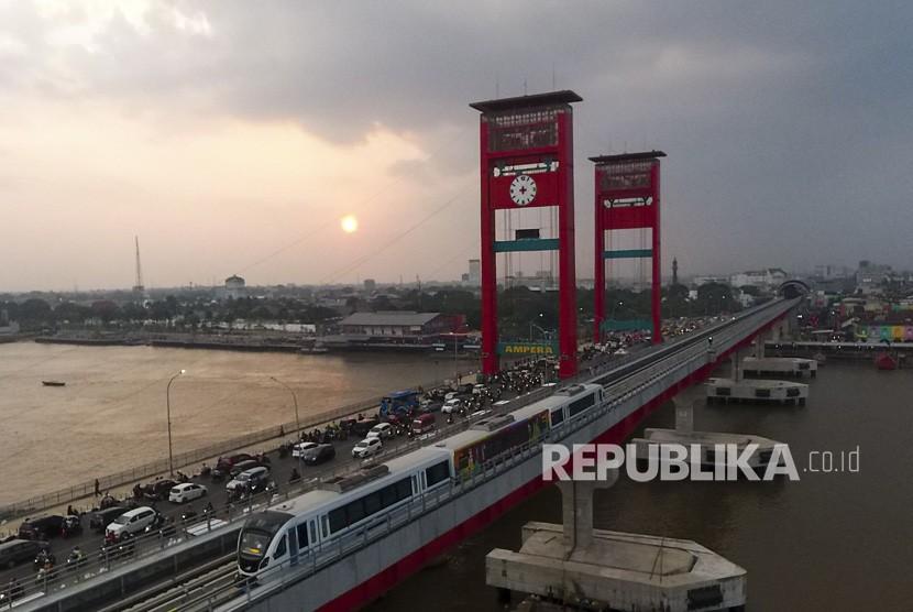 Rangkaian Light Rail Transit (LRT) Palembang melintas di atas Sungai Musi, Palembang, Sumatra Selatan, Senin (23/7).