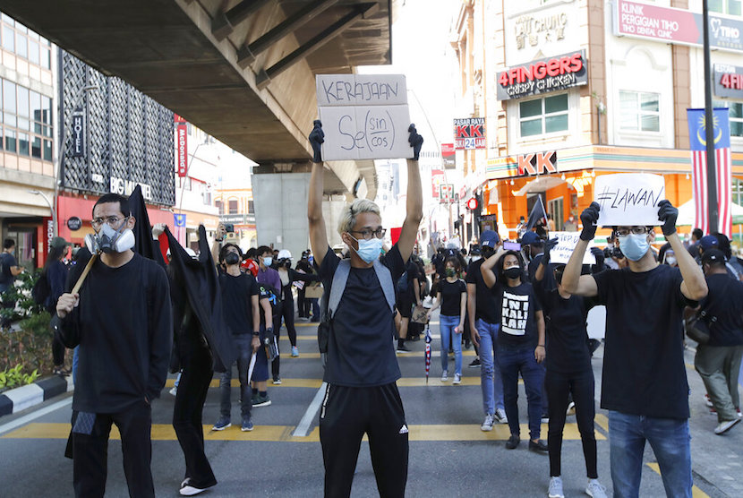 Ratusan anak muda berpakaian hitam berunjuk rasa dekat Lapangan Merdeka, Kuala Lumpur, Sabtu, (31/7/2021). Massa menuntut Perdana Menteri Muhyiddin Yassin mengundurkan diri karena dianggap gagal mengatasi pandemi covid-19.