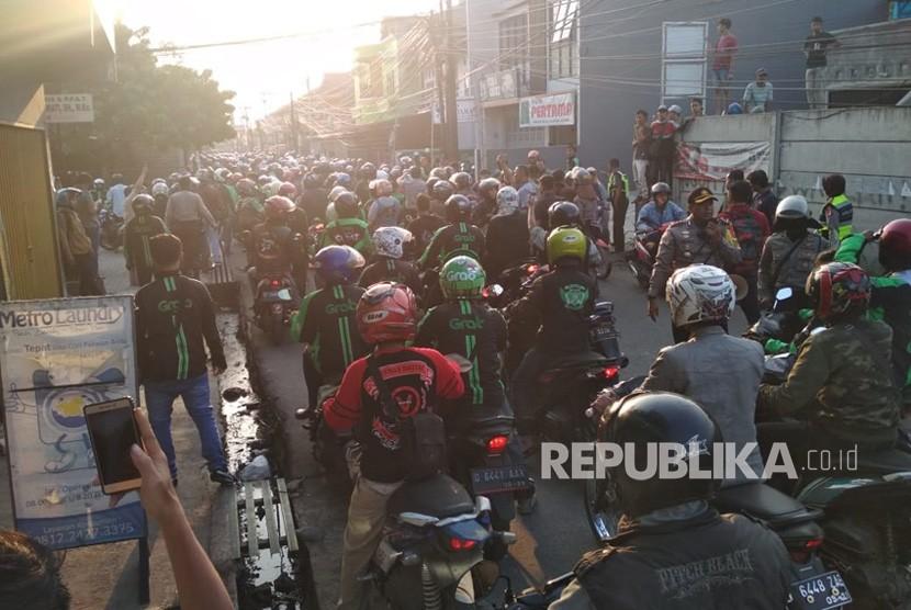 Ratusan pengemudi ojek online melakukan aksi solidaritas di jalan raya Bojongsoang, Kabupaten Bandung, Jumat (27/7). Mereka mendatangi jalan Cikoneng, tempat kejadian terjadinya pemukulan oleh oknum ojek pangkalan kepada ojek online.