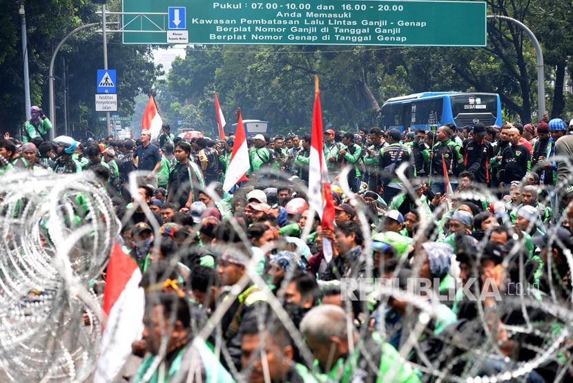 Ratusan pengemudi ojek online (Ojol) melakukan aksi unjuk rasa di depan Istana Merdeka, Jakarta, Selasa (27/3).