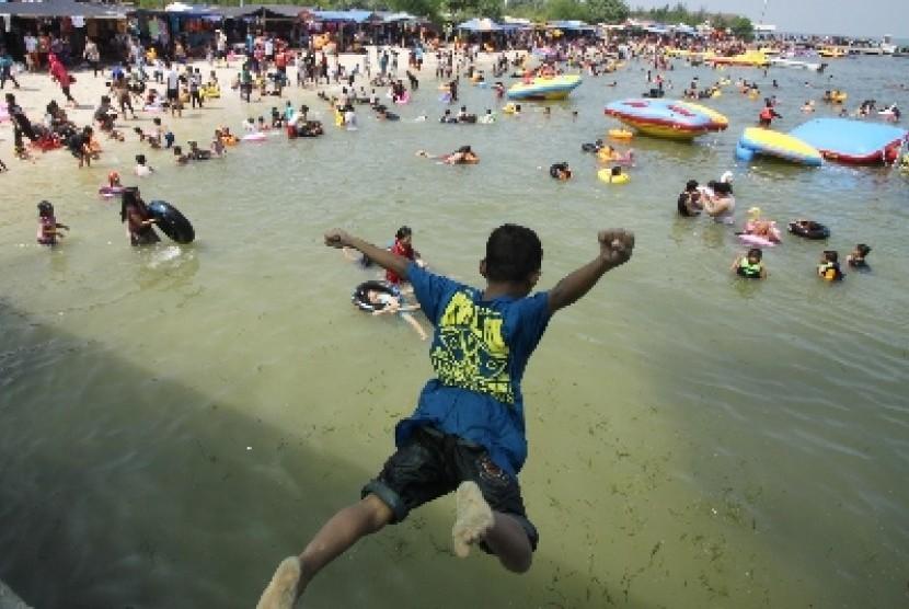 Ratusan pengunjung memadati pantai wisata Pulau Untung Jawa, Kepulauan Seribu, Jakarta, Kamis (31/7).