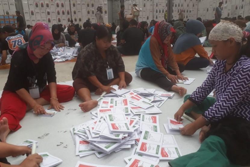 Ratusan warga tengah menyortir dan melipat surat suara pemilu 2019 di Gudang Logistik Komisi Pemilihan Umum (KPU) Kabupaten Bandung di Kampung Sawah, Soreang, Kabupaten Bandung, Kamis (14/3).
