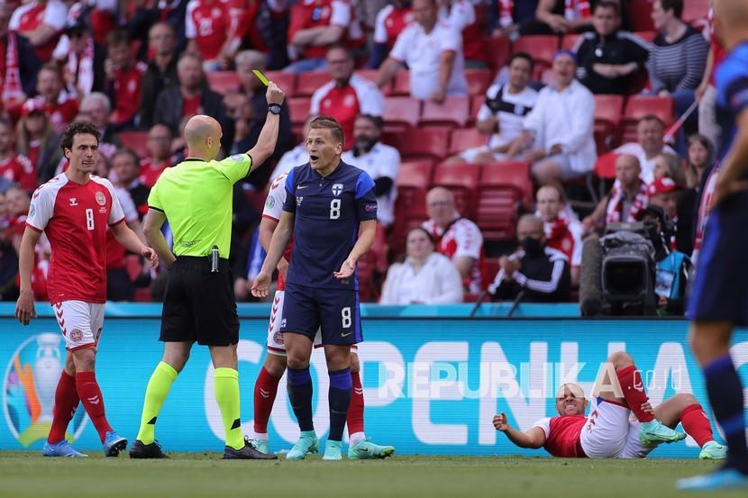 Reaksi pemain Finlandia Robin Lod saat menerima kartu kuning pada pertandingan grup B kejuaraan sepak bola Euro 2020 antara Denmark dan Finlandia di stadion Parken di Kopenhagen, Denmark, Sabtu (12/6).