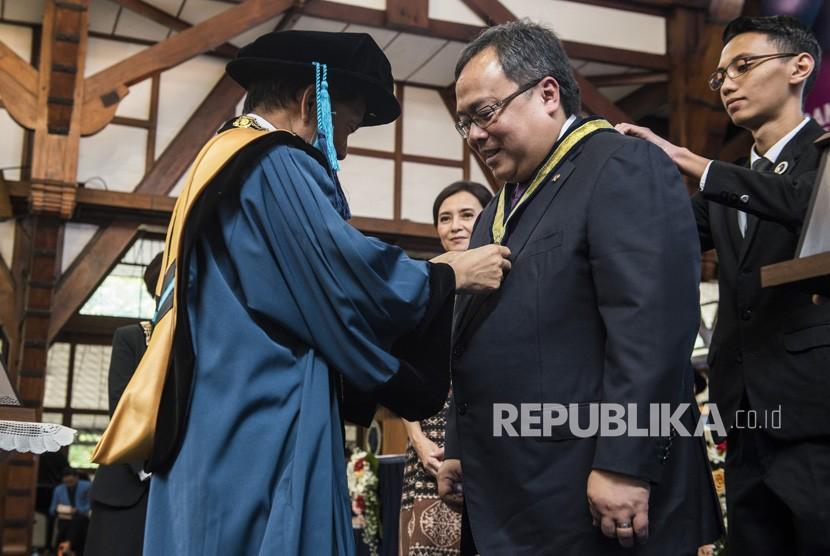 Rektor ITB Kadarsah Suryadi (kiri) menyematkan tanda penghargaan kepada Menteri Perencanaan Pembangunan Nasional (PPN)/Kepala Bappenas Bambang Brodjonegoro (kedua kiri) saat menerima penghargaan pada peringatan ke 98 Pendidikan Tinggi Teknik di Bandung, Jawa Barat, Rabu (4/7).