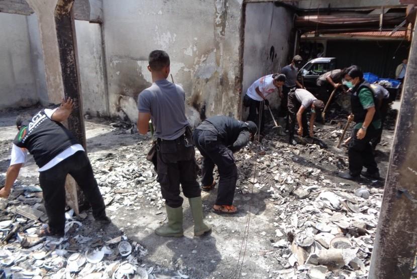 Relawan dan aparat kepolisian melakukan bersih-bersih kios Pasar Bendungan.