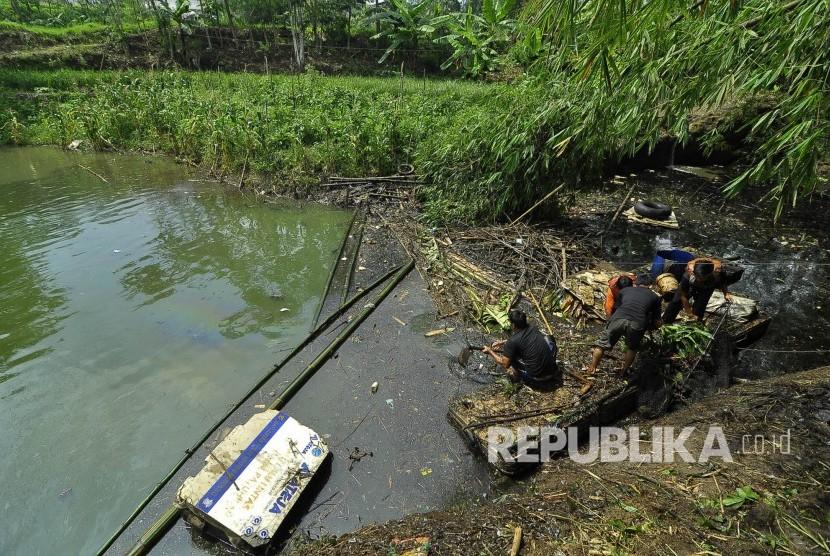 Relawan dan petugas damkar menangani tumpahan oli yang bocor dari pabrik tekstil dan mencemari waduk Saguling, Desa Laksanamekar, Kecamatan Padalarang, Kabupaten Bandung Barat, Selasa (4/4).