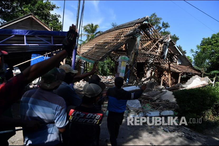 Relawan dan warga berusaha merubuhkan sebuah rumah yang rusak akibat gempa di Desa Kaliuling, Lumajang, Jawa Timur, Senin (12/4/2021). Warga mulai merubuhkan bangunannya yang rusak akibat gempa yang terjadi pada Sabtu (10/4) untuk mengantisipasi jatuhnya reruntuhan pascagempa.